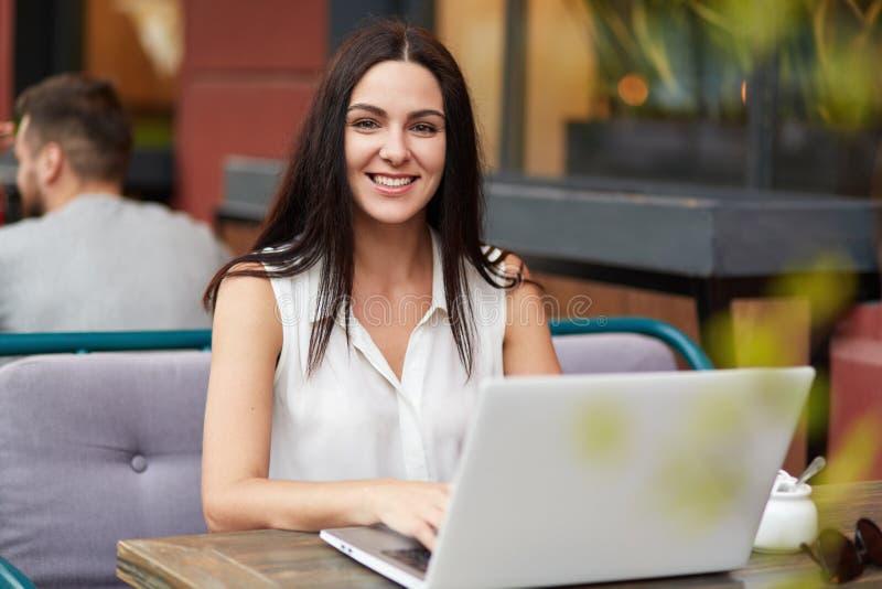 Erfolgreicher weiblicher Freiberufler arbeitet entfernt an Laptop-Computer, sitzt Café im im Freien, hat angenehmes Lächeln, geni stockfotos