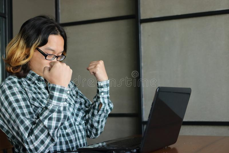 Erfolgreiches Geschäfts-Konzept Überzeugte asiatische Arbeitskraft, die Arme anhebt und glücklich gegen seins Arbeit im Büro glau stockbild