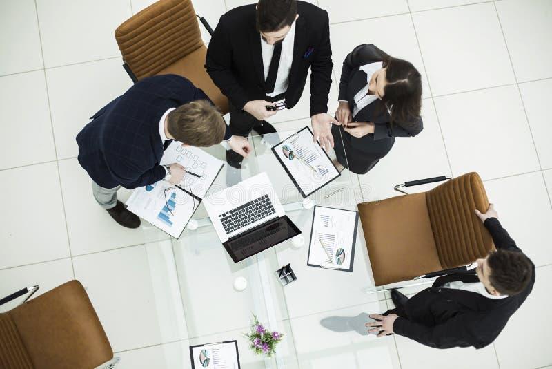 Erfolgreiches Geschäftsteam, das Grafiken bei einem Arbeitstreffen vermarktend sich bespricht lizenzfreie stockfotografie