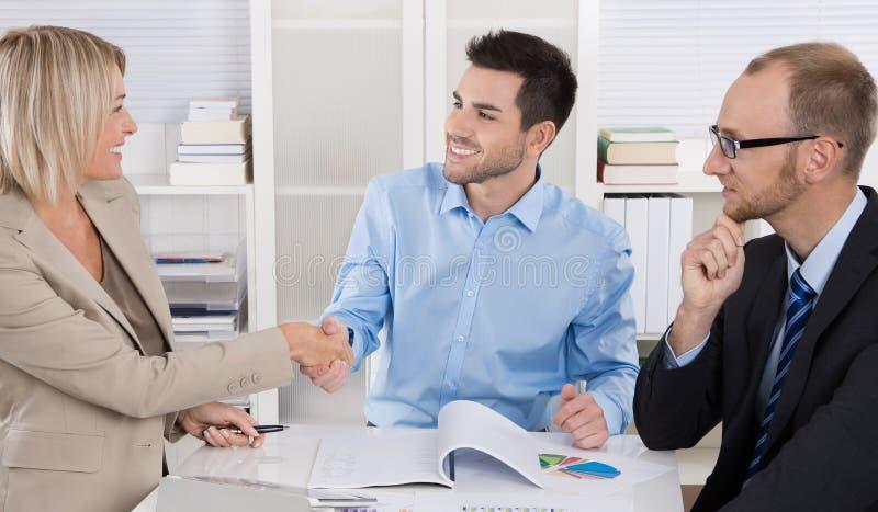 Erfolgreiches Geschäftsteam, das um eine Tabelle in einer Sitzung sitzt stockbild