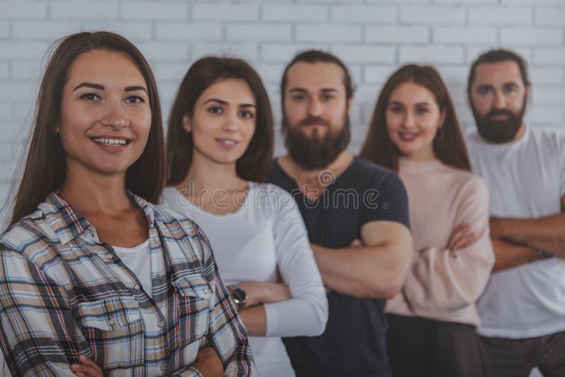 Erfolgreiches kreatives Geschäftsteam, das zur Kamera lächelt stockfotografie