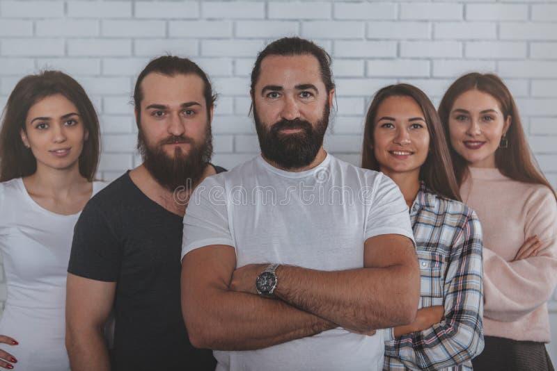Erfolgreiches kreatives Geschäftsteam, das zur Kamera lächelt stockfotos