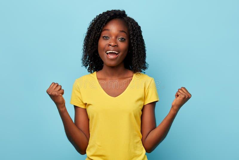 Erfolgreiches positives Mädchen, das seiend Sieger, lokalisiert auf blauem Hintergrund feiert stockbild