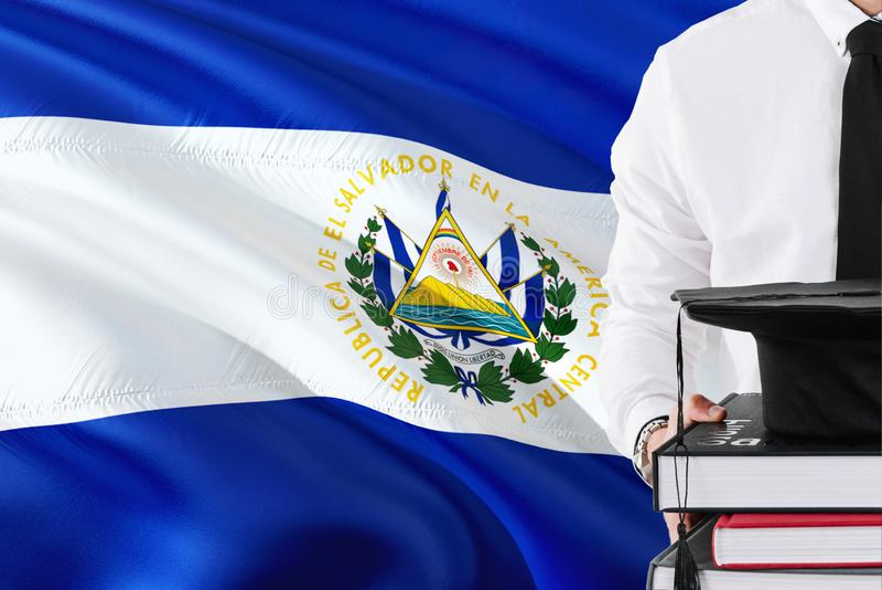 Erfolgreiches salvadorianisches Studentenausbildungskonzept Halten von Büchern und von Staffelungskappe über El Salvador Flaggenh stockfoto