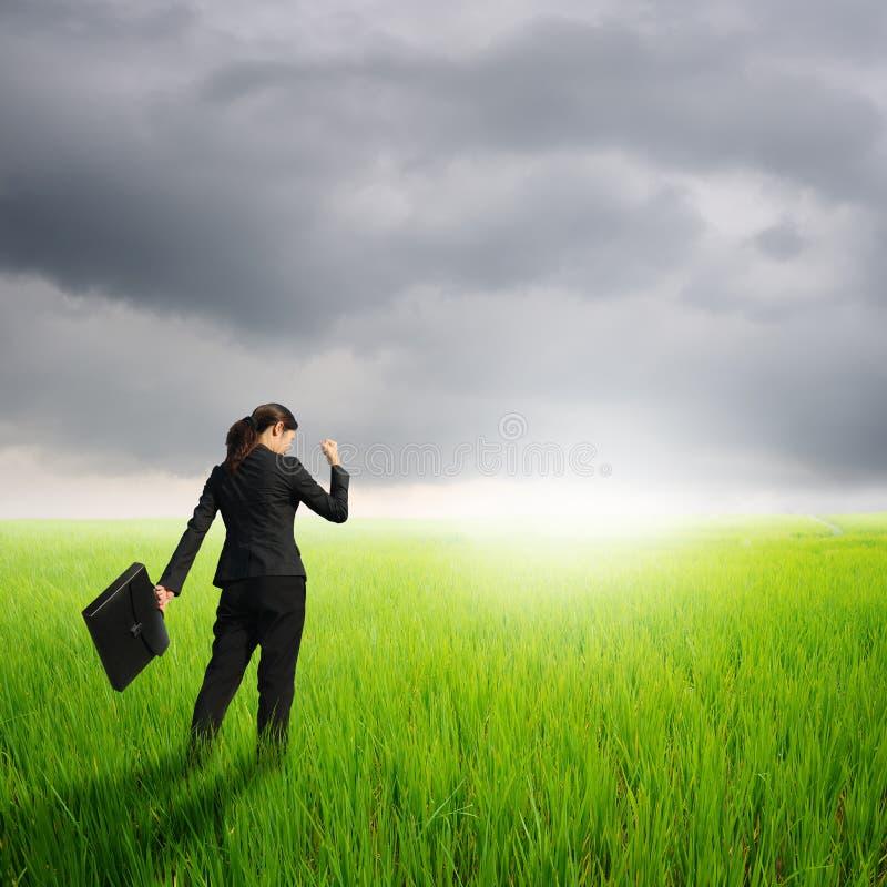 Erfolgs-Geschäftsfrau, die Tasche auf grünem Reis Gebiet und raincloud hält stockbild