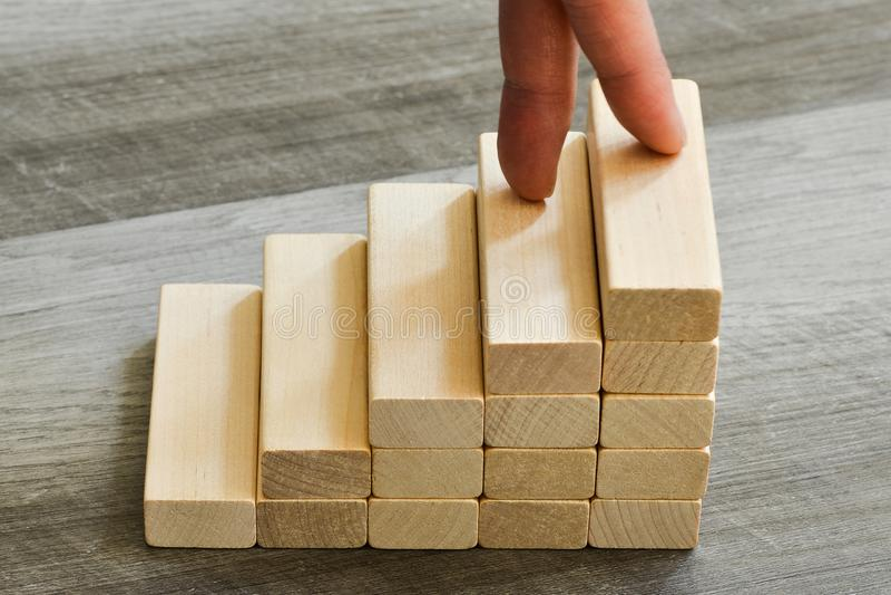 Erfolgs-Konzept - Finger, die bis zur Spitze des Treppenhauses über dunklem hölzernem Hintergrund klettern stockbild