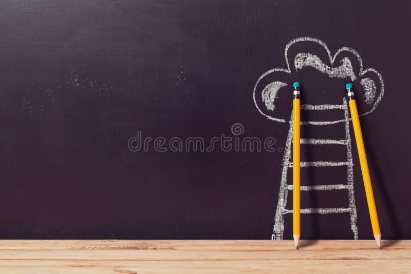 Erfolgskonzept mit Bleistiften und Leiter über Tafel stockbild
