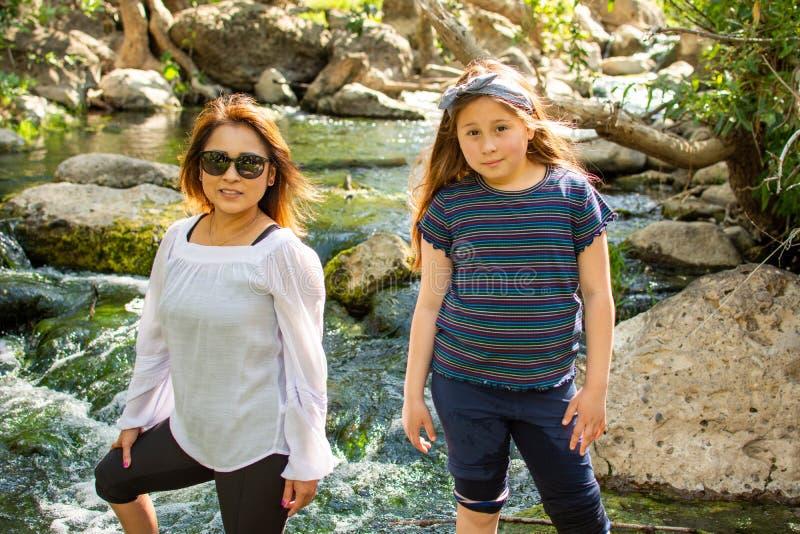 Erforschungsnatur der Frau und der Tochter zusammen in einem Strom oder einem Fluss stockfoto