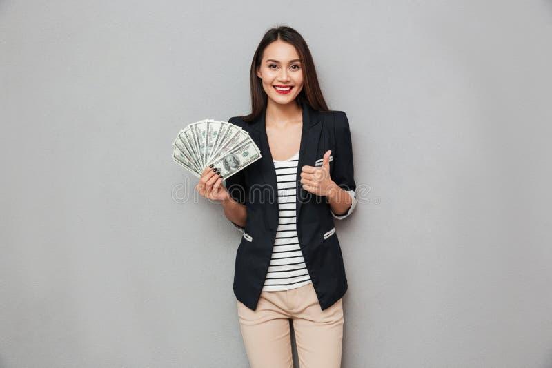 Erfreute asiatische Geschäftsfrau, die Geld hält und sich Daumen zeigt lizenzfreie stockbilder