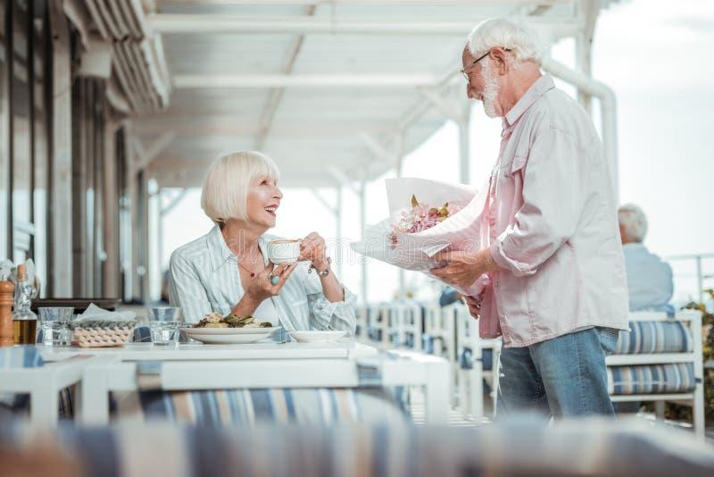 Erfreute Blondine, die ihren Ehemann betrachten stockfoto