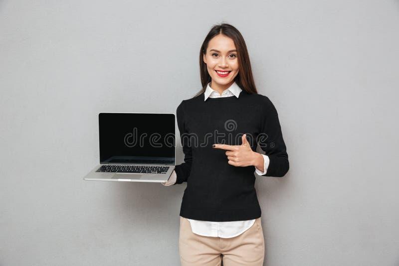 Erfreute Frau im Geschäft kleidet das Zeigen leeren Laptop-Computer Schirmes stockfotos