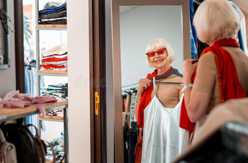 Erfreute graue behaarte Frau, die Sommerkleid vor ihr in passendem Raum des Einkaufsspeichers hält stockfotos
