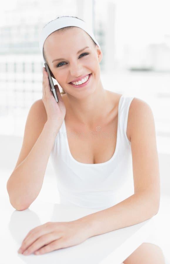 Erfreute hübsche Sportlerin, die einen Telefonanruf beantwortet lizenzfreie stockbilder