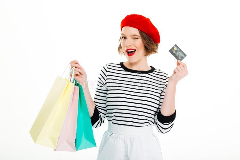 Erfreute Ingwerfrau mit den Paketen, die Kreditkarte halten lizenzfreie stockfotos