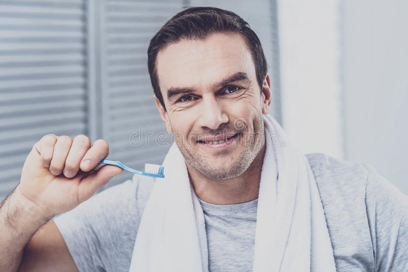 Erfreute männliche Person, die geht, Zähne zu säubern lizenzfreie stockfotografie