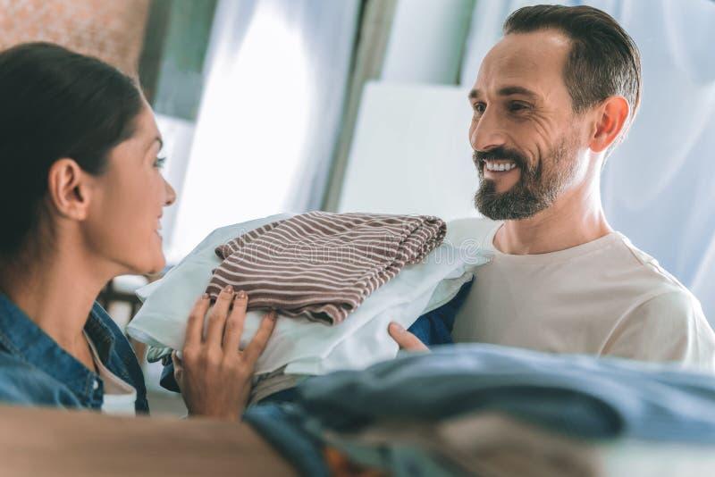 Erfreute männliche Person, die seiner Frau hilft lizenzfreies stockbild