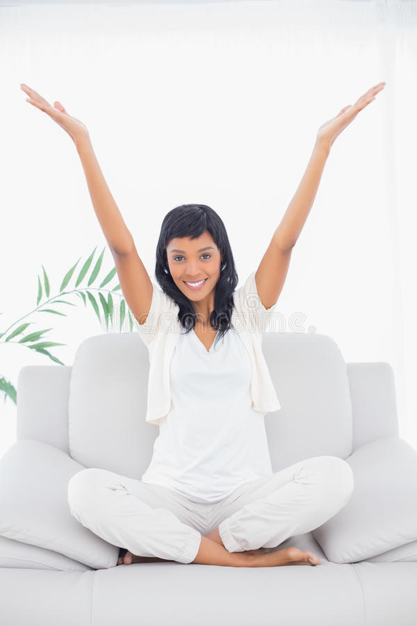 Erfreute schwarze behaarte Frau in der weißen Kleidung, die ihre Arme anhebt lizenzfreie stockbilder