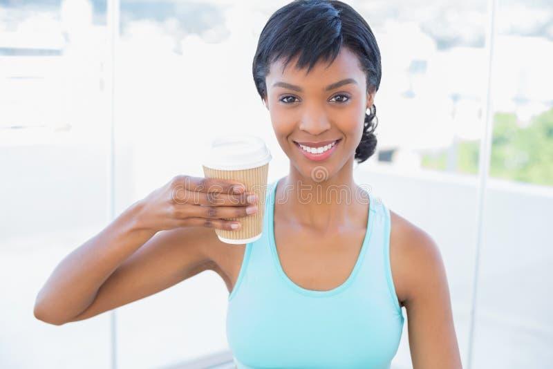 Erfreute schwarze behaarte Frau, die ein Getränk hält stockbild