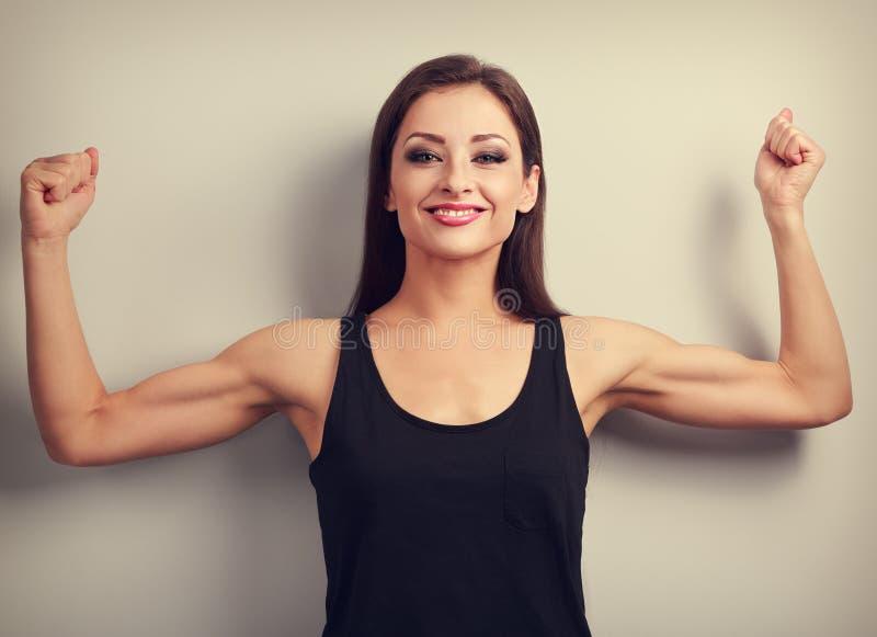 Erfreute starke Sitzfrau, die Muskelbizeps mit glücklichem smilin zeigt lizenzfreie stockfotos