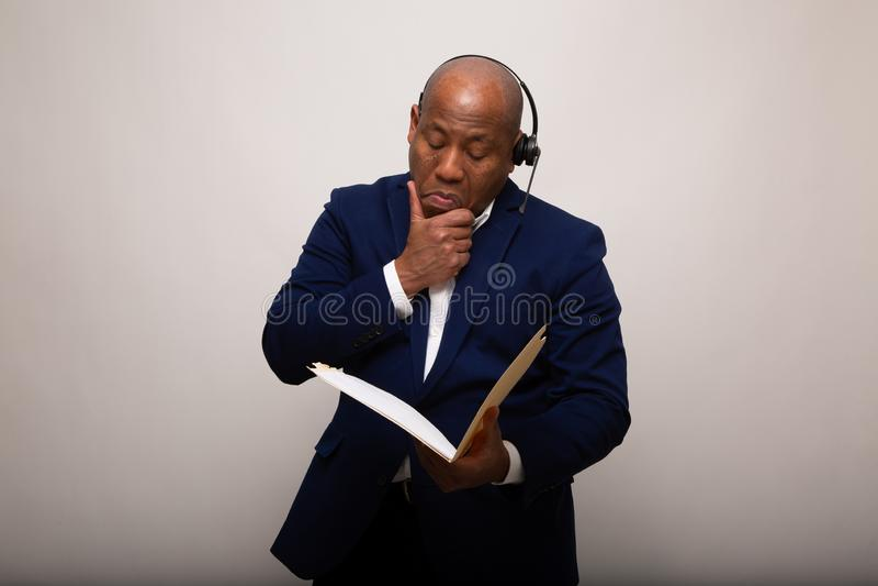 Erfreuter Afroamerikaner-Geschäftsmann Looks Through File stockfotos