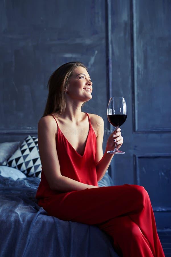 Erfreuter Brunette, der ein Glas Wein hält und weit schaut lizenzfreie stockfotografie