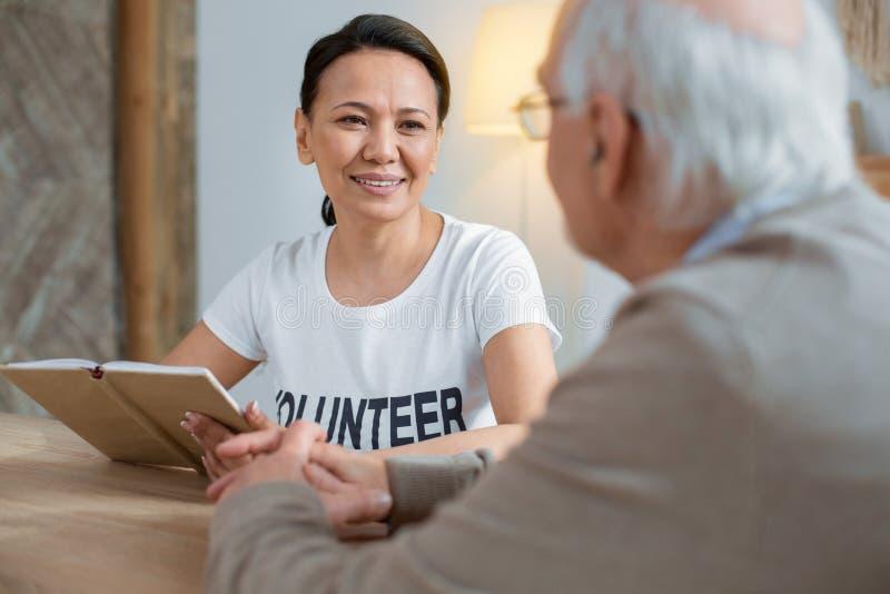 Erfreuter Freiwilliger, der ihre Arbeit erledigt lizenzfreies stockbild