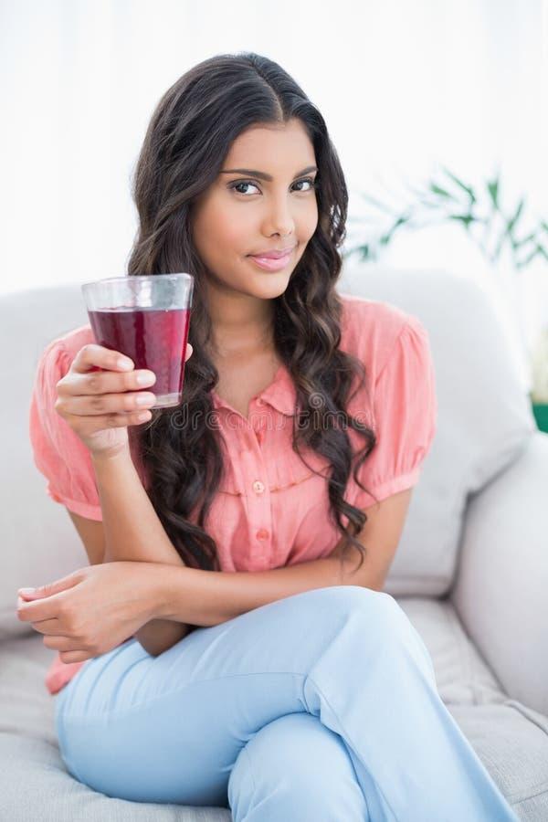 Erfreuter netter Brunette, der auf der Couch hält Glas Saft sitzt lizenzfreies stockbild
