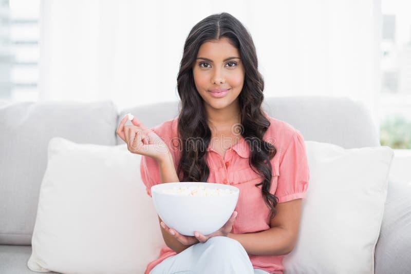 Erfreuter netter Brunette, der auf der Couch hält Popcornschüssel sitzt lizenzfreie stockfotografie