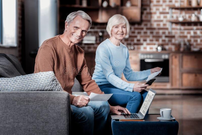 Erfreuter Pensionär, der seinen Computer verwendet stockfotografie