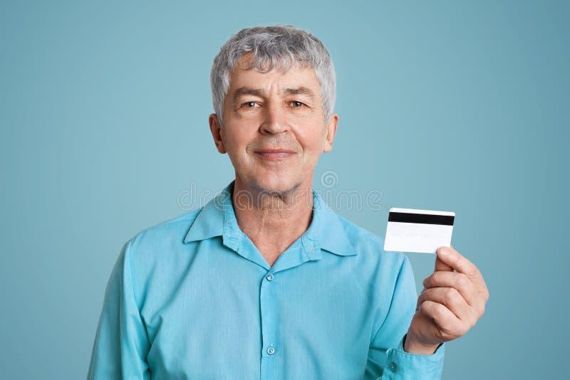 Erfreuter reifer Mann mit fröhlichem Ausdruck im formalen Hemd, Griffe schreiben die Plastikkarte gut, glücklich, Pension auf ihr lizenzfreie stockbilder