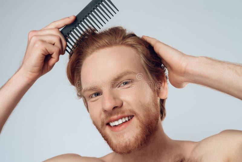 Erfreuter roter behaarter Mann kämmt Haar mit Kamm stockbilder