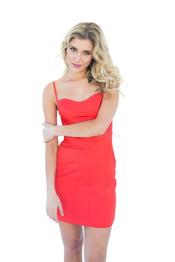 Erfreutes lächelndes blondes Modell, das Kamera betrachtet stockfotografie