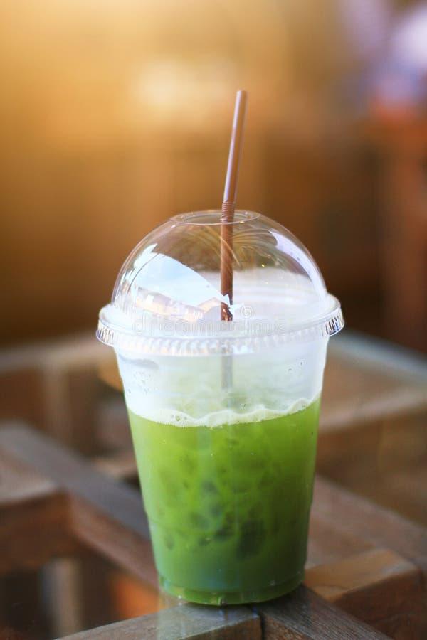 Erfrischung mit grünem Tee des Eises im Plastikglas auf dem Tisch stockfotos