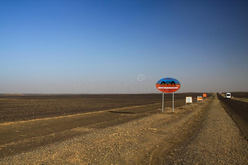 ERG CHEBBI SAHARA, MAROCCO - 25 SETTEMBRE 2011: Segnali stradali isolati Lost nella terra residua del deserto con l'orizzonte sen fotografia stock libera da diritti