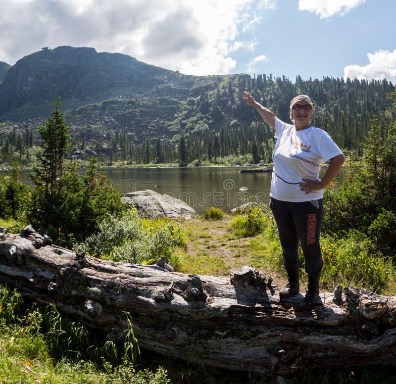 ERGAKI, RUSIA - 5 DE AGOSTO DE 2017: Una mujer mayor desconocida camina las montañas, participante en la competencia QUE SE ARRAS imagen de archivo libre de regalías