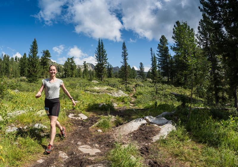 ERGAKI, RUSSIA - AUGUST 05 2017: Unknown girl walks the mountains, participant of the TRAILING contest SKAYRANFEST stock photography