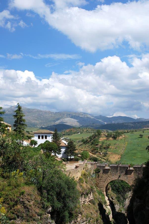 Erhöhte Ansicht der alten Brücke, welche die Schlucht mit Ansichten in Richtung zur Landschaft, Ronda, Spanien kreuzt stockfotos