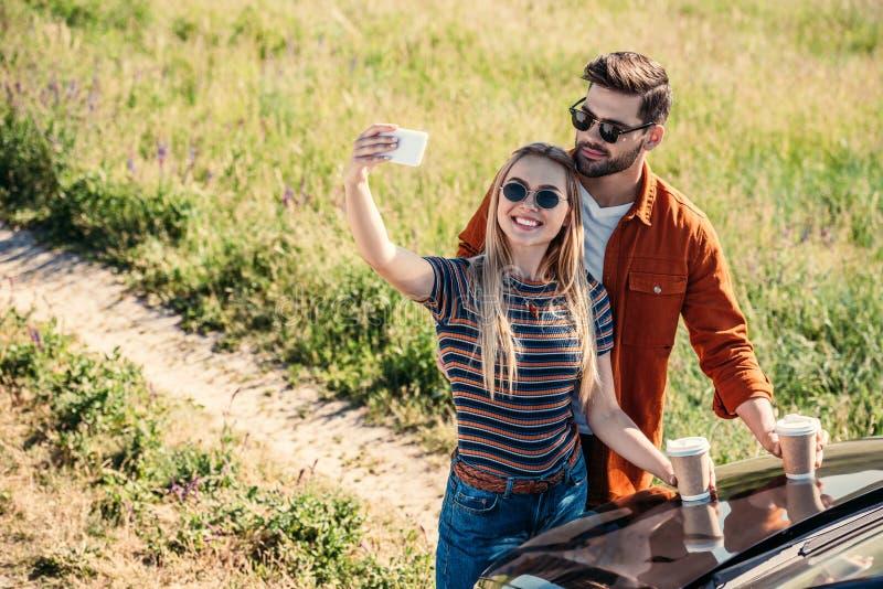 erhöhte Ansicht von stilvollen Paaren in der Sonnenbrille mit den Kaffeetassen, die selfie auf Smartphone nahe Auto auf ländliche stockfotografie