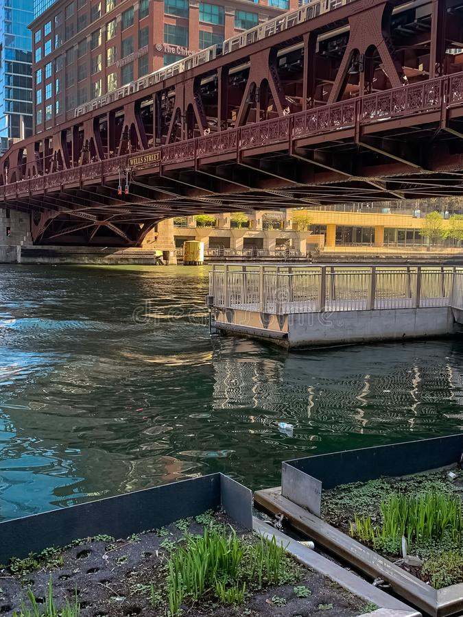 Erhöhter 'EL-Zug, der den Chicago River wo Flöße einer Plastikflasche kreuzt lizenzfreie stockfotos