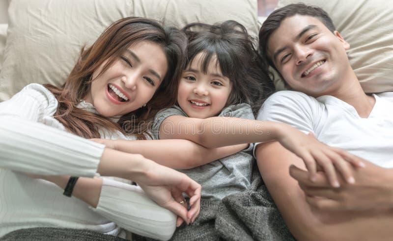 Erhöhtes Ansichtporträt der glücklichen Familie liegend auf Bett und oben schauend und Händchenhalten lizenzfreie stockbilder