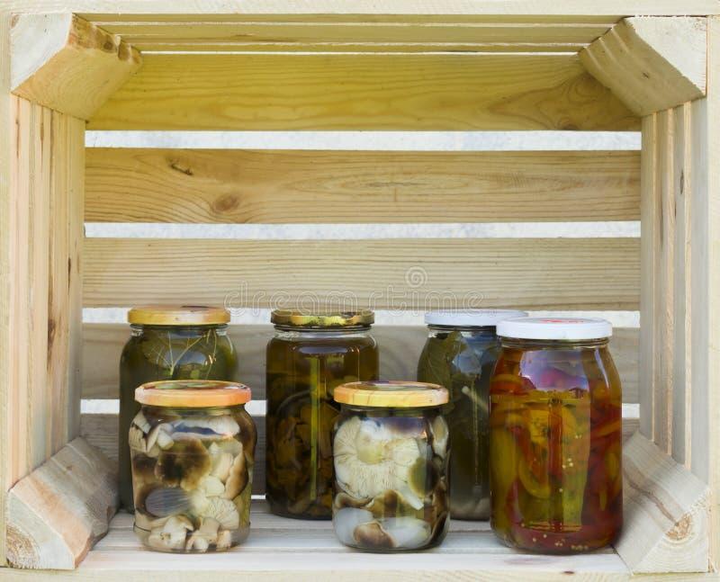 Erhalt von in Essig eingelegten Gurken und von Pilzen Essiggurkengläser lizenzfreie stockfotografie