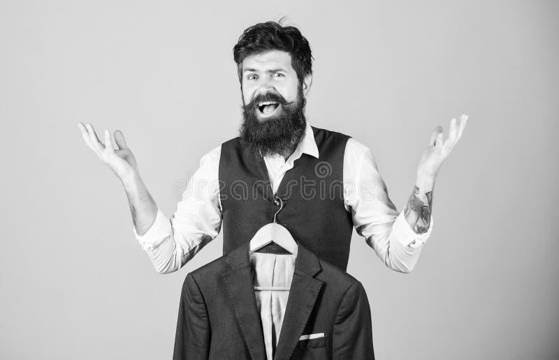 Erhalten aufgeregt über Mode Emotionaler Blick des bärtigen Mode-Modells Modedesigner, der hilft, Anzugsjacke zu w?hlen lizenzfreie stockfotografie