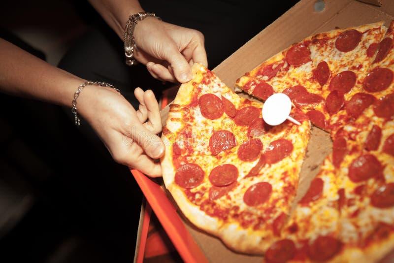 Erhalten einer Scheibe der frischen Pepperonipizza lizenzfreie stockfotografie