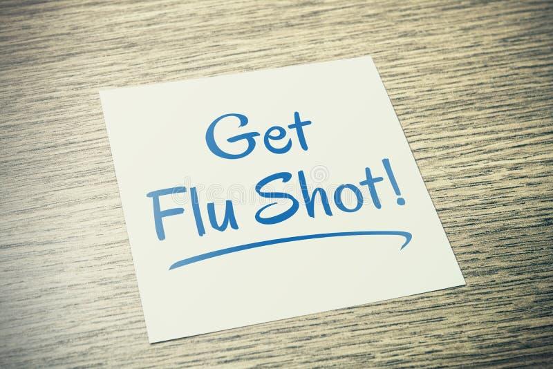Erhalten Sie Grippeimpfungs-Anzeige auf Papier auf Holztisch lizenzfreie stockfotografie