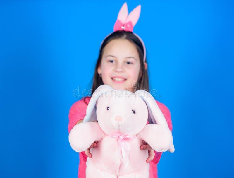 Erhalten Sie in Ostern-Geist Glückliche Kindheit Häschenohrzusatz Reizendes spielerisches Häschenkind umarmt weiches Spielzeug Hä lizenzfreie stockbilder