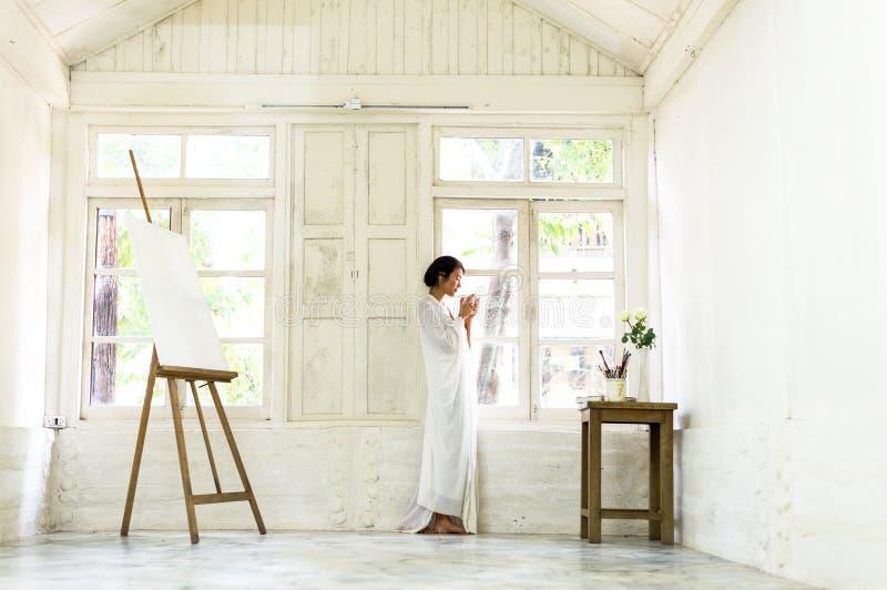 Erhalten warm mit frischem Kaffee Schöner trinkender Kaffee der jungen Frau und Schauen durch ein Fenster lizenzfreies stockfoto