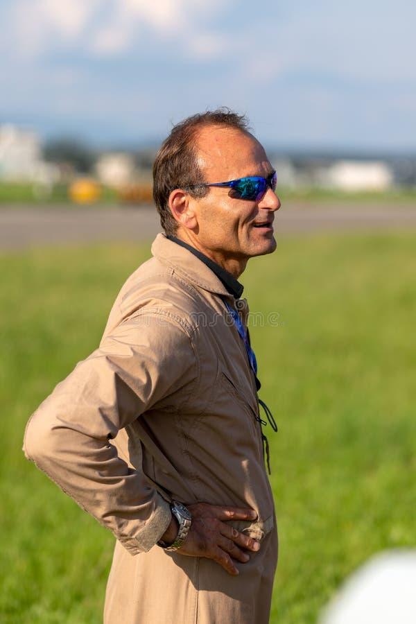 Eric Goujon, piloto francés anterior de la fuerza aérea que vuela para la colección de los toros que vuela de avión en el hangar  foto de archivo libre de regalías