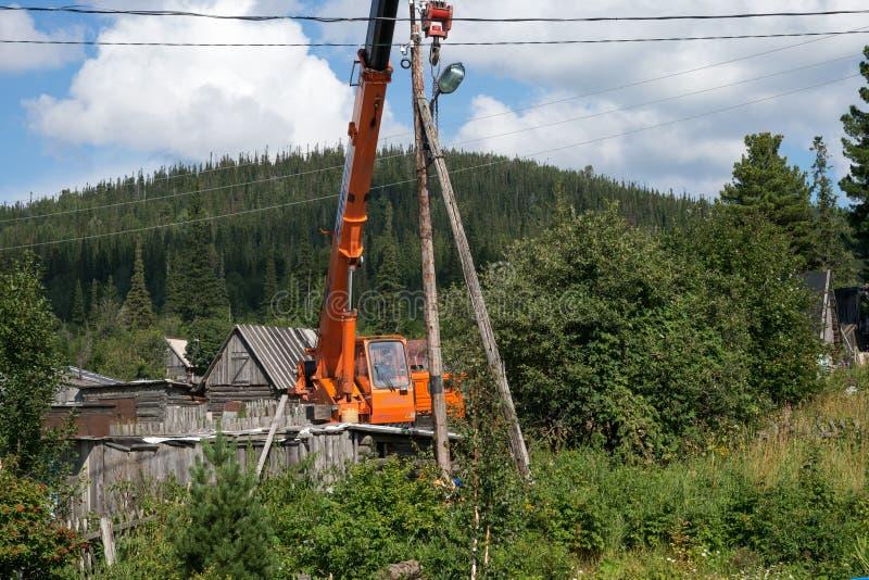 Erigiendo la grúa lista para desmontar la vieja transmisión de madera elévese en las cercanías del pueblo imagen de archivo