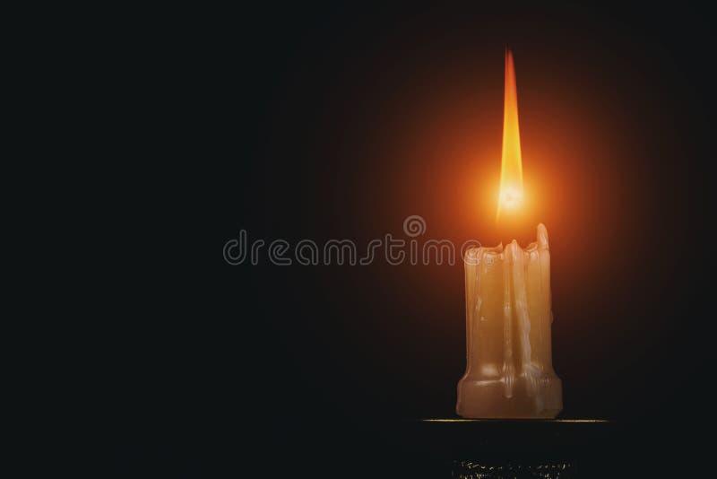 Erinnerungsschuß von einer Kerzenflamme auf schwarzem Hintergrund stockfoto