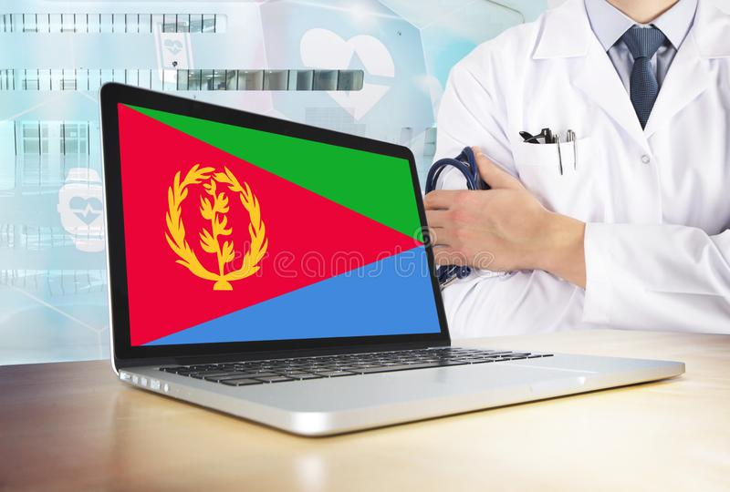 Eritrea healthcare system in tech theme. Eritrean flag on computer screen. Doctor standing with stethoscope in hospital. Cryptocurrency and Blockchain concept royalty free stock photography
